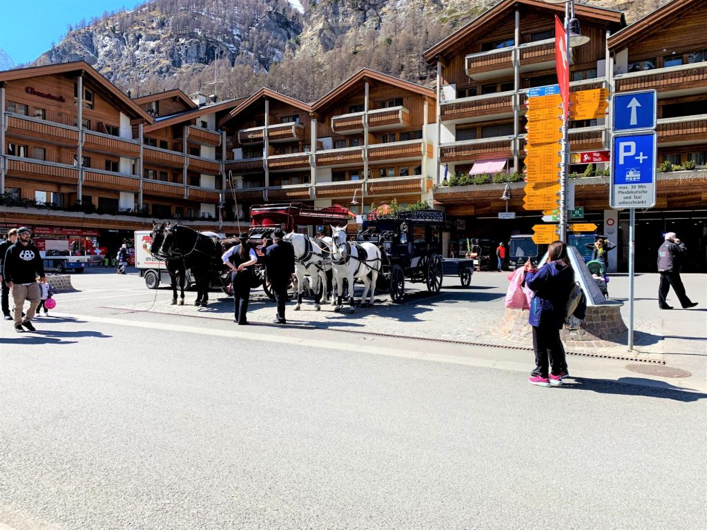 Zermatt - outside the Bahnof. Horse driven carriages waiting for hotel guests!